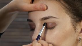 Berufsmake-upkünstler macht Augenmake-up auf einem Kundengesicht Schönheitsmodeindustrie stock footage