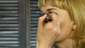 Berufsmake-upkünstler wenden Pulver mit Bürste auf einem Kundengesicht an Schönheitsmodeindustrie stock video footage