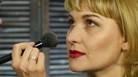 Berufsmake-upkünstler wenden Pulver mit Bürste auf einem Kundengesicht an Schönheitsmodeindustrie stock footage