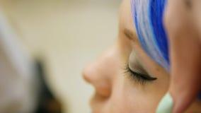 Berufsmake-upperson ein junges Mädchen mit dem blauen Haar stock footage