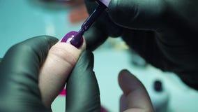 Berufsmanikürist, Manikürearbeit in den schwarzen Handschuhen am Schönheitssalon Dunkles Purpur, schöne rosa Nägel, Abschluss her stock footage