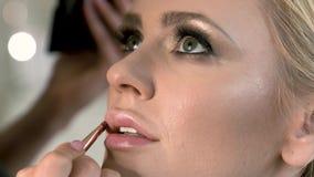 Berufsmaskenbildner, der flüssigen Lippenstift am Modell anwendet Nahaufnahmeschönheit und Modekonzept stock video