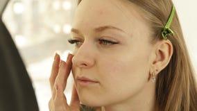 Berufsmaskenbildner, der Kosmetikcreme auf junger Frau der Problemhaut in der Umkleidekabine aufträgt Schließen Sie herauf Make-u stock video footage