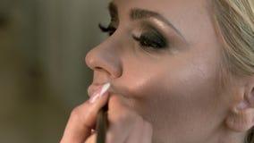 Berufsmaskenbildner, der Lippenzündkapsel für flüssigen Lippenstift anwendet Zündkapsel unter Lippenstift Nahaufnahmeschönheit un stock video footage