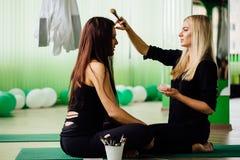 Berufsmaskenbildner, der mit schöner junger Frau arbeitet Eignungsmodelle, aero Yoga Sitzen Sie im Lotussitz Stockfotografie