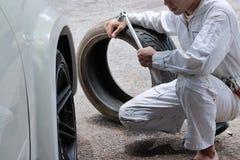 Berufsmechaniker im einheitlichen haltenen Schlüssel und im Reifen am Reparaturgaragenhintergrund Stockfotografie
