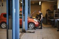 Berufsmechaniker Repairing Car Engine in der Garage stockfoto