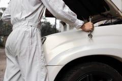 Berufsmechanikermann im weißen einheitlichen haltenen Schlüssel mit Auto in der offenen Haube am Reparaturgaragenhintergrund Lizenzfreie Stockbilder