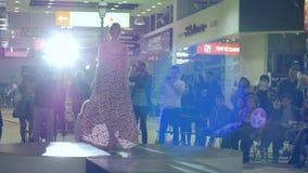 Berufsmodell auf der Brücke, zur Schau stellend entwirft elegante Kleidung, das schöne Modell, das entlang Podium im Kleid geht stock footage