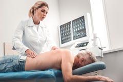 Berufsphysiotherapeut, der Massage für älteren Mann tut lizenzfreie stockbilder
