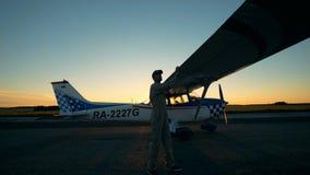 Berufspilot überprüft Flügel eines Flugzeugs Ein Mann betrachtet den Flügel und überprüft sie bei der Stellung auf einer Rollbahn stock video
