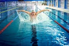Berufspolospieler, männlicher Schwimmer, die Schmetterlingsanschlagtechnik am Hallenbad durchführend, schwimmende Praxis Stockfoto