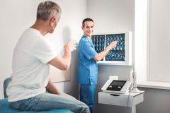 Berufsröntgenstrahlspezialist, der geduldige Ergebnisse zeigt stockbilder