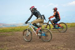 Berufsradfahrer, welche die abschüssige Mountainbike auf den Gebirgspfad reiten stockbild