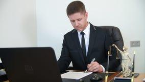 Berufsrechtsanwaltlesung und unterzeichnendes Dokument auf Arbeitstabelle im Rechtsanwaltsbüro stock footage