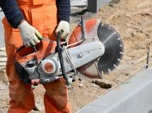 Berufsrundschreiben sah für Arbeit über Beton in den Händen an der Arbeitskraft Lizenzfreie Stockfotos