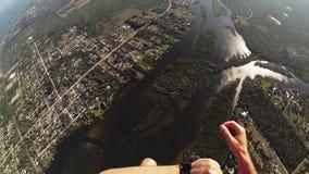 Berufsskydiver, der über Flachland mit Fallschirm abspringt landschaft Extreme Liebhaberei stock video