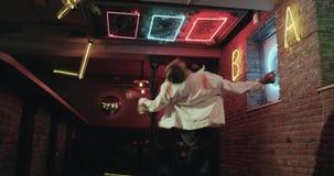 Berufstänzer mit erstaunlichem Choreografietanzen in der Stange mit erstaunlicher lichttechnischer Ausrüstung 4K Rotes Epos stock video footage