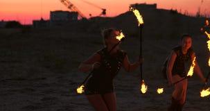 Berufstänzerfrauen machen eine Feuershow und eine pyrotechnische Leistung am Festival mit brennenden funkelnden Fackeln stock footage