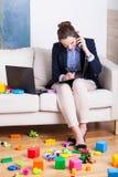 Berufstätige Frau unter den Spielwaren des Kindes Stockbild