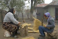 Berufstätige Frauen stellen Besen auf traditionelle Art her lizenzfreie stockfotos