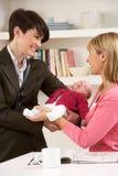 Berufstätige Mutter, die Schätzchen mit Kindermädchen lässt Lizenzfreies Stockbild