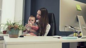 Berufstätige Mutter mit Kleinkind im freundlichen Büro des Babys, arbeitende moderne Mutterschaft des sucsessful weiblichen Unter stock video