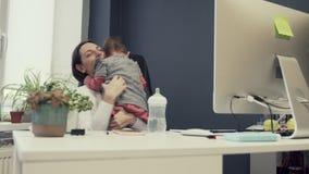 Berufstätige Mutter mit Kleinkind im freundlichen Büro des Babys, arbeitende moderne Mutterschaft des sucsessful weiblichen Unter stock footage