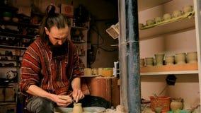 Berufstöpfer, der Becher mit Spezialwerkzeug in der Tonwarenwerkstatt schnitzt Lizenzfreie Stockbilder