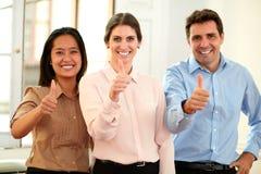 Berufsteam, das an Ihnen mit dem okaydaumen lächelt Lizenzfreies Stockfoto
