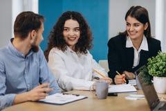 Berufsteam -- Firmenkundengeschäft-Schablone B Glückliche kreative junge Leute, die im Team beim Sein im Büro arbeiten stockfoto