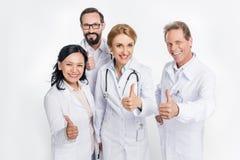 Berufsteam von Doktoren, die sich Daumen zeigen und an der Kamera lächeln stockbilder