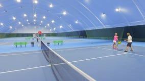 Berufstrainer unterrichtet erwachsenen Mann, Tennis zu spielen stock video footage