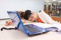 Berufstätige Frau, die auf einer Tabelle schläft Lizenzfreies Stockfoto