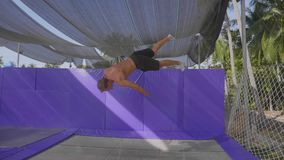Berufsturner, der auf die Trampoline springt und Tricks in der Zeitlupe tut stock video footage