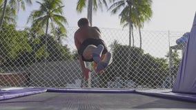 Berufsturner, der auf die Trampoline springt und Tricks in der Zeitlupe tut stock video