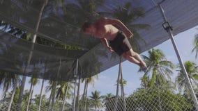 Berufsturner, der auf die Trampoline springt und Tricks in der Zeitlupe tut stock footage