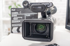 Berufsvideokamera mit einem clapperboard lizenzfreies stockbild