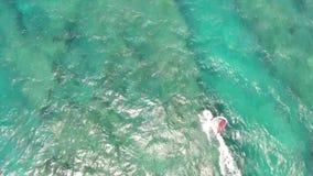 Berufswindsurfer, der in den ruhigen Wellen des hawaiischen Meerblicks des Türkisblau-Ozeanwassers im Luftbrummennocken der Spitz stock video footage
