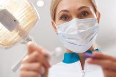 Berufszahnarzt, der an seiner zahnmedizinischen Klinik arbeitet lizenzfreie stockfotografie