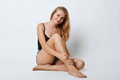 Beruhigende blonde Frau mit den schlanken Beinen, die auf dem weißen Hintergrund, untersuchend direkt Kamera mit frohem Ausdruck  Stockbilder
