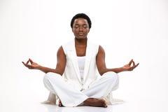 Beruhigte recht afrikanische Frau, die in der Lotoshaltung sitzt und meditiert Stockfotografie