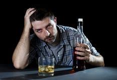 Berusad alkoholiserad man med den whiskyexponeringsglas och flaskan i alkoholböjelse och alkoholismbegrepp Royaltyfri Fotografi