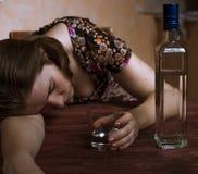 Berusad kvinna som rymmer hennes alkoholdryck och sover på tablen Arkivbilder