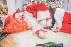 Berusade Santa Claus som ligger på golv och att sova Hans påse är under huvudet Flaska som ligger på matta royaltyfri bild