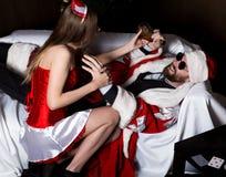 Berusade Santa Claus som ligger på soffan, sexig kvinna för kvinnlig sjuksköterska i karnevaldräkten, försök att vakna upp honom arkivfoto
