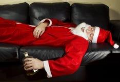 Berusade Santa Claus som poserar med en flaska av whisky Royaltyfria Bilder