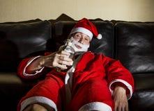 Berusade Santa Claus som poserar med en flaska av whisky Royaltyfri Foto
