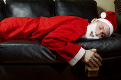 Berusade Santa Claus som poserar med en flaska av whisky Arkivfoton