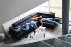 Berusade vänner som sover på det Sofa In Messy Room After partiet royaltyfria bilder